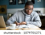 Stock photo focused millennial african american student in glasses making notes writing down information from 1079701271