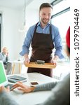Small photo of Portrait of handsome male waiter bringing drinks to modern young woman working with laptop in cafe