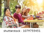 Small photo of Multicultural happy friends eating and drinking beers at barbecue dinner at sunset - Young people having meal together outdoor - Focus on asian girl - Summer lifestyle, party and friendship concept