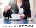 Small photo of The woman stirs a spoonful of coffee and tea. The woman will sweeten her coffee with sugar. Misuse of sugar, use of sweeteners.