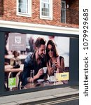 Small photo of Wokingham, Peach Street, Berkshire, England - April 27, 2018: Careys Saxons Court new homes development advertising poster on construction site perimeter hoarding