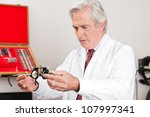 Mature optometrist examining trial frame for eye examination in the clinic - stock photo