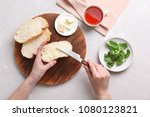 woman spreading butter on slice ... | Shutterstock . vector #1080123821