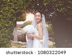 Beautiful Attractive Asian Bride Woman wearing wedding dress and holding bouquet smile and happiness in wedding day