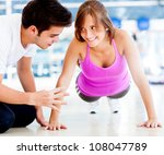 Woman exercising at the gym with her personal trainer - stock photo