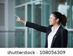 Portrait of Indian business woman pointing with her arm out stretched. - stock photo
