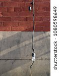 Small photo of Light bulb (unlit) and frayed wire hanging in front of exterior brick and cement wall, with diagonal shadows. Urban and gritty. With space for copy/text.