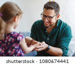 Small photo of Father's day. Happy family daughter giving dad a gift on holiday