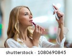 Attractive young woman looking into a compact mirror and putting on her lipstick