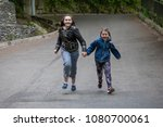 two girls are runing  on the... | Shutterstock . vector #1080700061