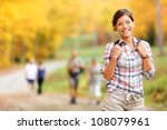 Autumn hiking girl. Female hiker looking around in forest in autumn colors. Beautiful young woman on hike. - stock photo