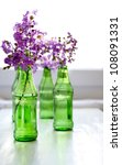 Purple Flowers In Green Bottles