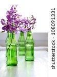 Purple Flowers In Green Bottles