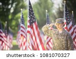 Hispanic American Female Soldier in uniform saluting in front of American flags - stock photo