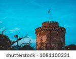 Small photo of Historic crenelated round tower on a fort or castle with a flag flying from the battlements or ramparts at dusk against a blue ky