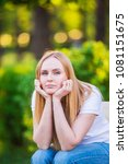 Small photo of Emotions of the girl, fatigue, boredom, depression, sadness. Attractive bored young blond Caucasian woman holding her head with hands, sits outside in the park.