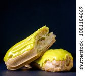 Small photo of Pistachio eclair in glaze on black background, close up. Traditional French dessert