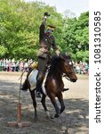 Small photo of WARSAW, POLAND - MAY 01, 2018: Polish cavalryman (uhlan) of 1930s cuts stick by sabre on a gallop. Cavalry show in Royal Lazienki park during Labor day celebration.