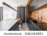 Stock photo kitchen interior with black cabinets steel tap and wooden table in dining area 1081365851