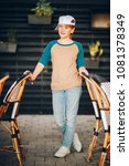 Small photo of Outdoor portrait of funny preteen girl wearing multi raglan top and white cap