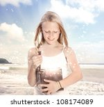Happy Young Blonde Girl Opening a Gift Box on the Beach - stock photo