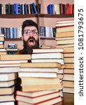 Small photo of Nerd concept. Man, nerd on surprised face between piles of books in library, bookshelves on background. Teacher or student with beard wears eyeglasses, sits at table with books, defocused.