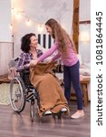 Small photo of Sincere care. Energetic girl holding blanket while crippled woman staring at her