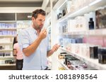 elegant man choosing perfume in ... | Shutterstock . vector #1081898564