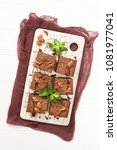 Small photo of Brownie sweet chocolate dessert with walnuts and meant leaves on retro board with copy space on pastel beige background. Beautiful banner with delicious brown cocoa baked pastry.