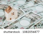 wooden house model on pile of... | Shutterstock . vector #1082056877