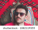 handsome hipster lying on rug... | Shutterstock . vector #1082119355