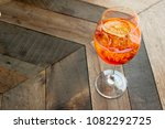 """Small photo of Florence, Tuscany / Italy. - May 3, 2018. Classic Italian aperitif """"aperol stpritz"""" with ice and a slice of orange in t large round glass on a wooden table in a bar in Italy"""