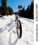 Small photo of Mountain bike standing in frozen snow against blue sky. Hidden asphalt road under sow cover. Extreme adrenalin sports