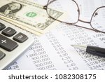 Small photo of Financial statements, expend reports with modern pen, calculator, glasses and US money dollar. Concepts of accounting, audit , tax planning and marketing budget management.