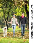Stock photo young couple holding hands and walking a dog in a park 108235295