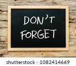 """Small photo of text """"don't forget"""" on black chalkboard with wooden background. meeting remind reminder note concept"""