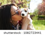Stock photo attractive hipster young woman in sunglasses kissing jack russell terrier puppy in park green lawn 1082723441