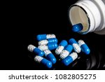 Medical pills spilling from a bottle on a black background - stock photo