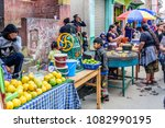 Small photo of Santiago Sacatepequez, Guatemala - November 1, 2017: Local women dressed in traditional clothing make corn tortillas next to other vendors in street during the giant kite festival on All Saints' Day.