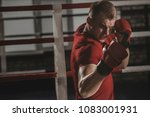 boxer trains blows in the gym.... | Shutterstock . vector #1083001931