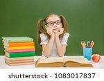 pensive little girl with books... | Shutterstock . vector #1083017837