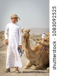 Small photo of Ibri, Oman, 28th April 2018: young omani man with his camel before a race