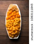 Small photo of Cheese balls / rings, Corn Puff with crispy salty Wheel fryums. Served in a white plate or wooden bowl. Selective focus