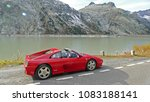 Bern Kanton in the Alps, Switzerland - 2015. Oct 15: Red sports car parking in the alpine road next to a lake. Ferrari 348 GTS. - stock photo