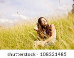Beautiful happy young woman sitting on grass in park - stock photo