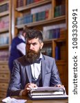 Small photo of Writer working on new book with bookshelves on background. Author types novel or poem. Man with beard and strict face sit in library and work with typewriter, close up. Writers routine concept.
