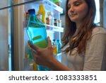 teenage girl taking water from... | Shutterstock . vector #1083333851