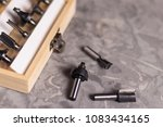 Small photo of Set of steel router bit for milling cutter in rectangle wooden box with metal lock near three bits on old broken worn gray concrete floor with copy space