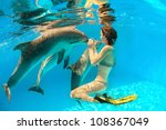 girl touches a dolphin's nose... | Shutterstock . vector #108367049