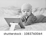 baby with tablet pc on the bed | Shutterstock . vector #1083760064